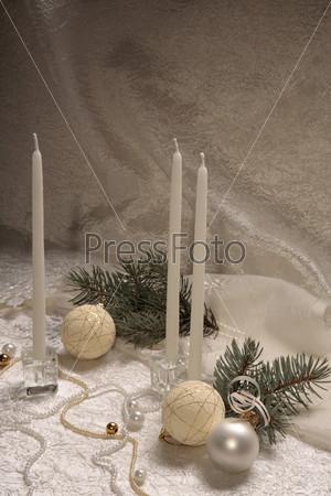 Белые новогодние шары, белые свечи, бусы и елочные ветки