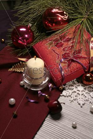 Фотография на тему Красные новогодние шары, белая свеча, елочные ветки и красная декоративная подушка