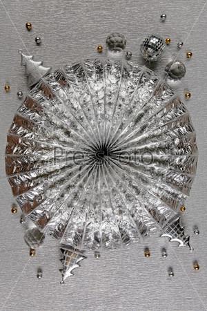 Серебряная круглая абстрактная поверхность с елочными игрушками, серебряными и золотыми бусинами