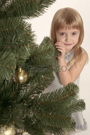 Девочка, выглядывающая из-за елки