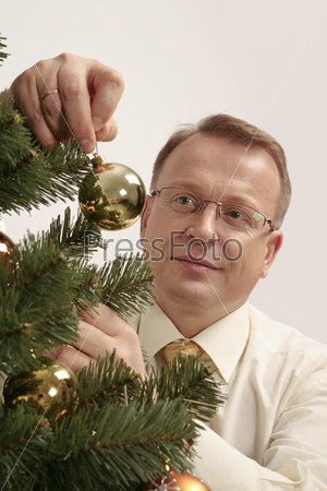 Мужчина вешает елочный шар на елку