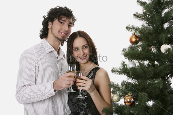 Мужчина и женщина с бокалами шампанского рядом с елкой