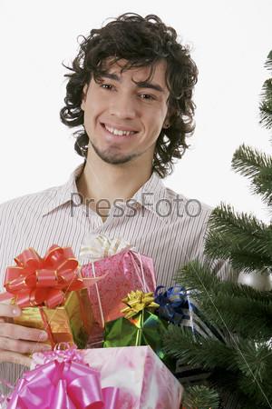 Мужчина с подарками рядом с елочными ветками