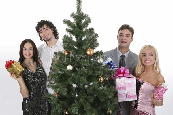 Две пары мужчин и женщин с подарками рядом с елкой