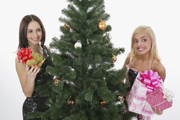 Две девушки с подарками рядом с елкой