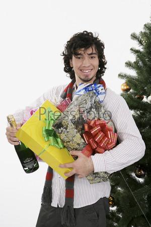 Мужчина с подарками и бутылкой шампанского рядом с елкой