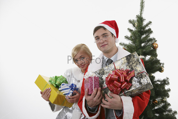 Мужчина, одетый в костюм деда мороза, и женщина, одетая в костюм снегурочки, с подарками перед елкой