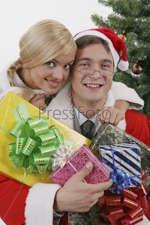 Мужчина, одетый в костюм деда мороза, с подарками и женщина