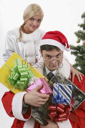 Мужчина, одетый в костюм деда мороза, с подарками и девушка, одетая в костюм снегурочки