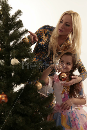 Мама с дочкой наряжают елку