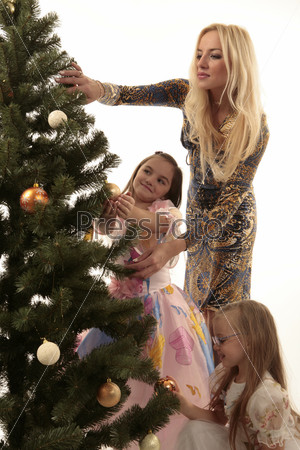 Мама и две дочери наряжают елку