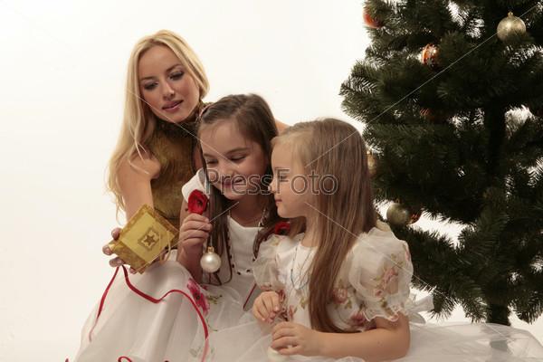 Мама и две дочери рядом с елкой