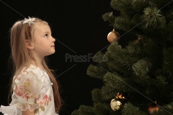 Девочка рядом с елкой на черном фоне