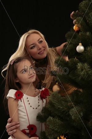 Мама и дочка смотрят на елку
