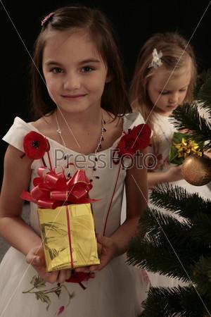 Две девочки с подарками рядом с елкой