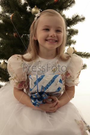 Девочка с подарком на фоне елки
