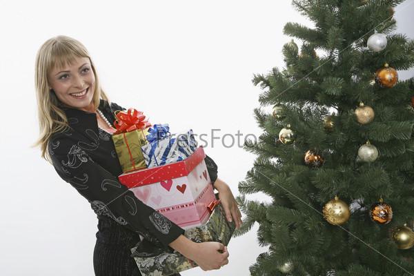 Девушка с подарками рядом с елкой