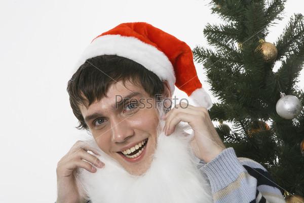 Молодой человек в новогодней шапке рядом с елкой