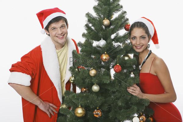 Молодой человек и девушка в новогодних шапках рядом с елкой