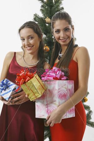 Две девушки с подарками перед елкой
