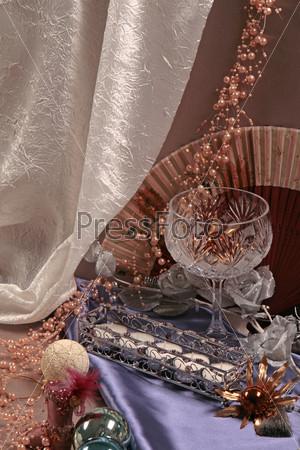 Хрустальный бокал, свечи, веер, розовые бусы, новогодние игрушки