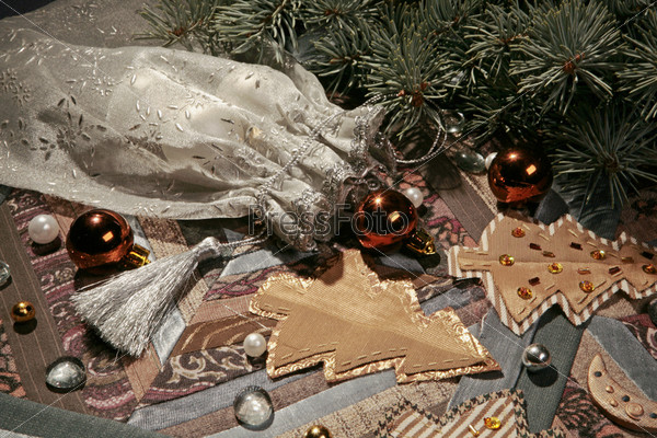 расшитый белый мешочек с серебряной кистью, оранжевые шары, игрушечные елки, еловая ветвь