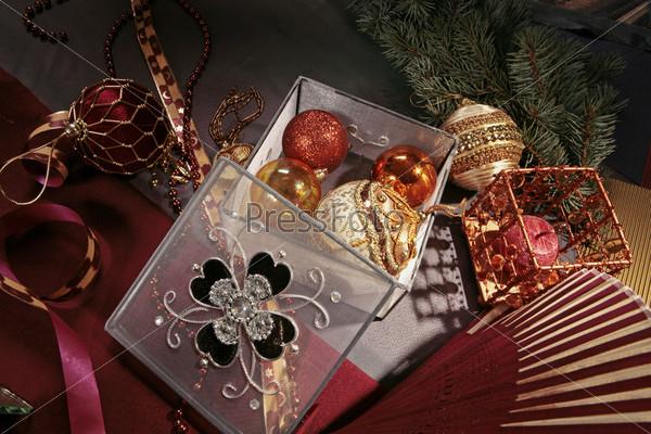 Фотография на тему открытая прозрачная шкатулка с елочными шарами, подсвечник с красной свечой, красно-белый веер, еловая ветвь
