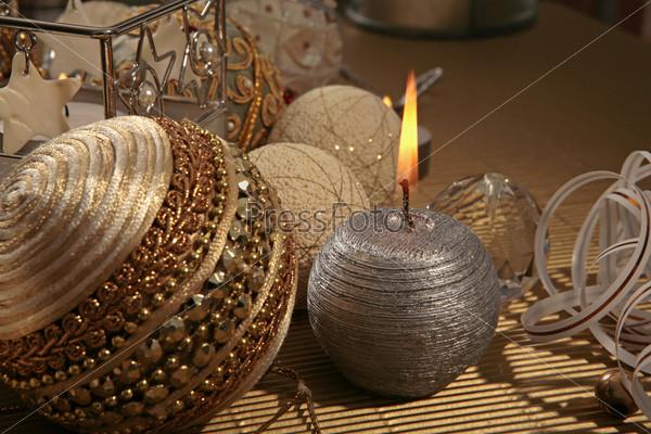 Горящая серебряная свеча, золотистый елочный шар