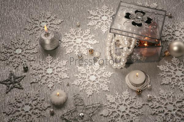 Серебряные горящие свечи, снежинки, прозрачная шкатулка с жемчужными бусами