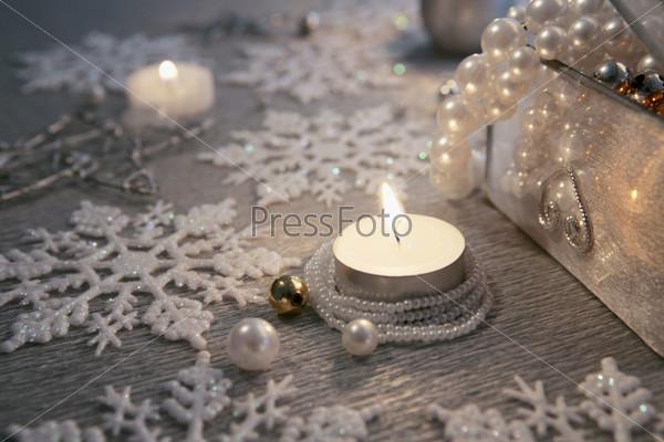 Горящая свеча, обернутая жемчужной нитью, снежинки, шкатулка с жемчугом
