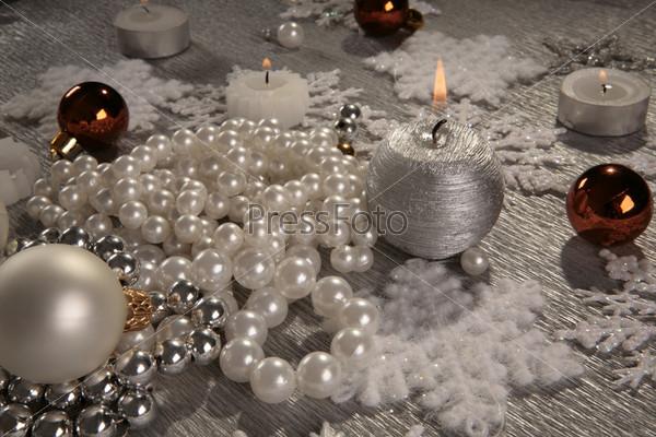 Горящие свечи, шары, гора жемчужных и стальных бус
