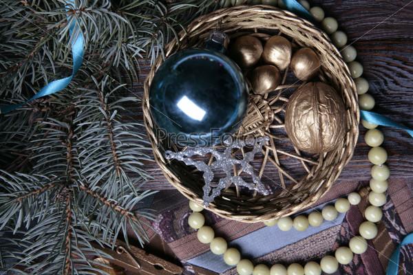Плетеная корзина с синим новогодним шаром и позолоченными орехами, нитка бус, еловая ветвь