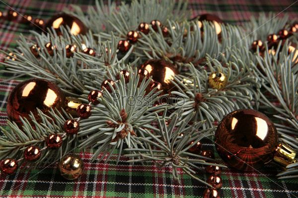 Еловая ветка, красные новогодние шары и бусы