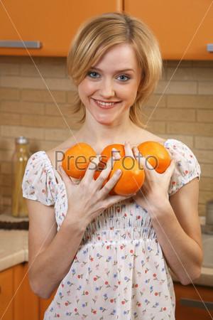 Фотография на тему Девушка на кухне с апельсинами