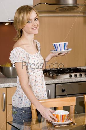 Молодая женщина накрывает на стол