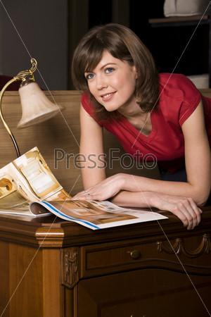 Молодая женщина смотрит журнал