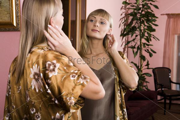Молодая женщина в халате у зеркала