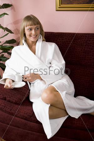 Молодая женщина на диване пьет кофе