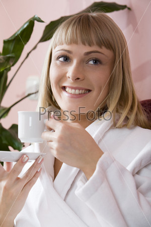 Молодая женщина в белом с чашкой кофе