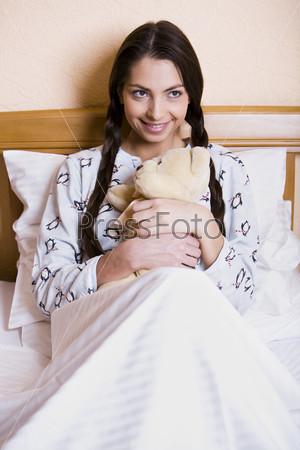 Девушка с плюшевым медведем готовится спать