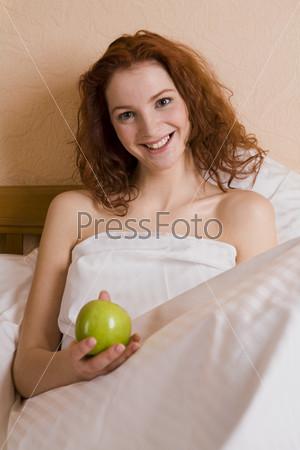 Девушка с яблоком в спальне