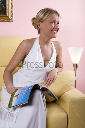 Девушка в белом платье читает журнал