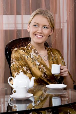 Девушка пьет чай за столиком дома
