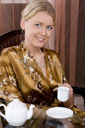 Молодая женщина в шелковом халате с чайной чашкой в руке