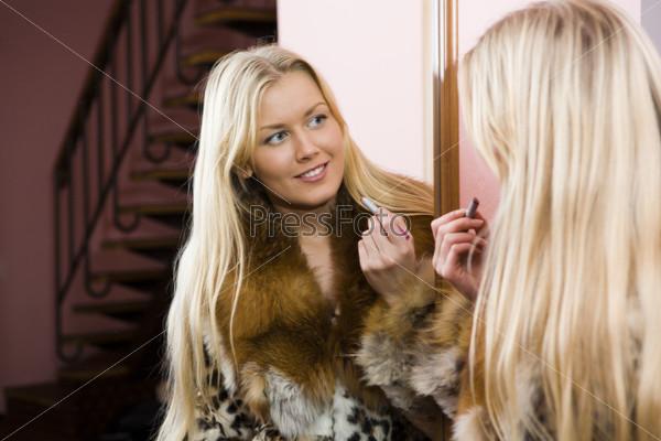 Красивая девушка в шубе перед зеркалом в прихожей с губной помадой в руке