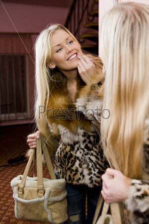 Красивая девушка в леопардовой шубе перед зеркалом в прихожей красит губы