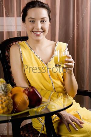 Молодая женщина сидит в кресле перед стеклянным столиком с фруктами и стаканом сока в руке