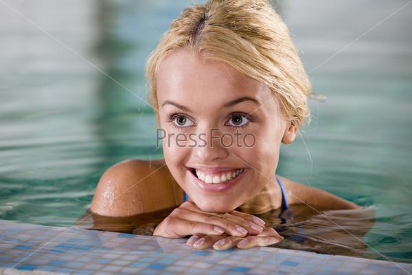 Жизнерадостная девушка у бортика бассейна
