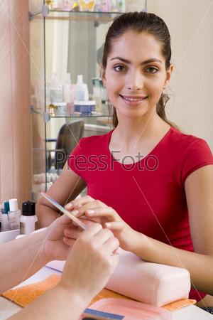 Девушке в красном делают маникюр