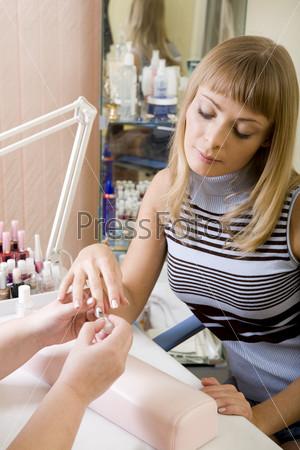 Блондинке делают маникюр в салоне красоты